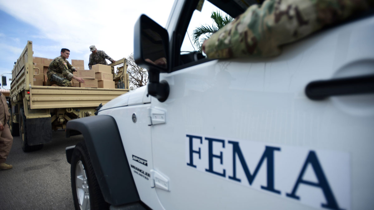 In this Oct. 5, 2017, file photo, Department of Homeland Security personnel deliver supplies to Santa Ana community residents in the aftermath of Hurricane Maria in Guayama, Puerto Rico.