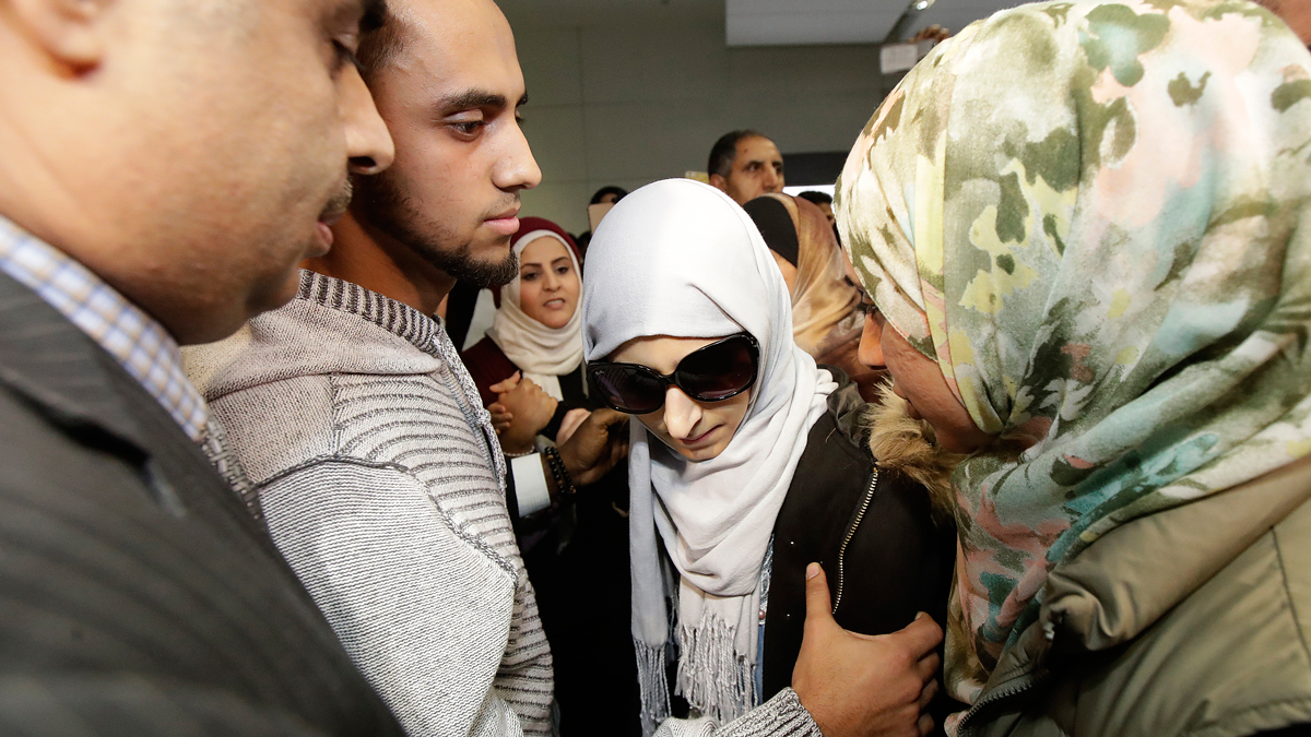 Shaima Swileh, center, stands with her husband Ali Hassan, second from left, after Swileh arrived at San Francisco International Airport in San Francisco, Wednesday, Dec. 19, 2018. Swileh is the Yemeni mother who won her fight for a waiver from the Trump administration's travel ban that would allow her to go to California to see her dying 2-year-old son.