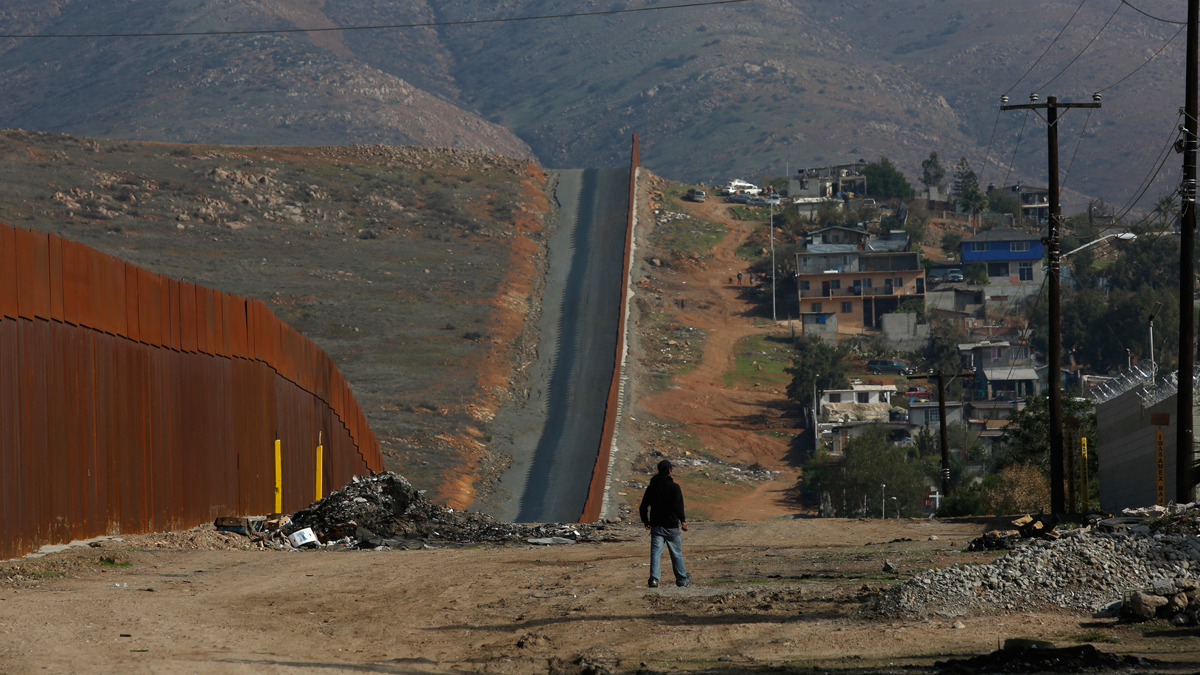 This Dec. 12, 2018, file photo shows a man walk next to the U.S. border wall in Tijuana, Mexico.