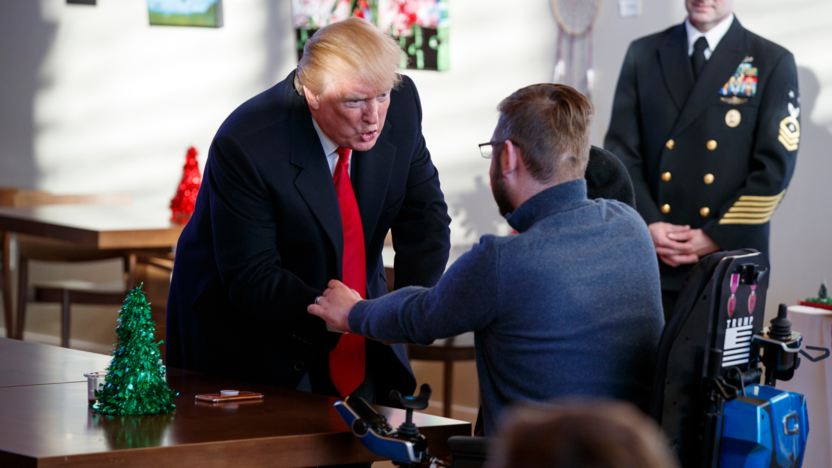 In this Thursday, Dec. 21, 2017, file photo, President Donald Trump meets retired U.S. Marine Corps Sgt. John Peck and his wife Jessica as Trump visits with wounded service members and their families during a visit to Walter Reed National Military Medical Center in Bethesda, Md. Trump this year became the first president to not visit with troops at Christmastime since 2002.